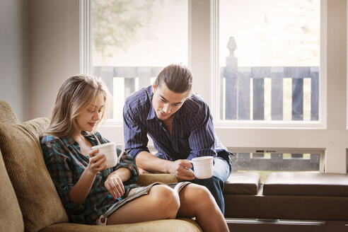 Couple reading magazine while drinking coffee at home - CAVF10028