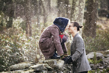 Side view of romantic couple in forest during winter - CAVF10061