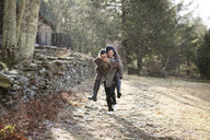 Man piggybacking girlfriend at forest during winter - CAVF10064