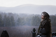 Thoughtful woman standing by forest in foggy weather - CAVF10070