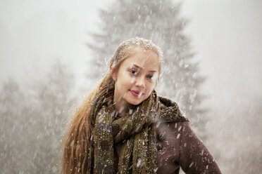 Portrait of happy woman in forest during winter - CAVF10079