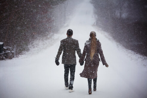 Rear view of couple holding hands while walking on snowy field - CAVF10082