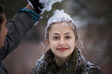 Man putting snow on girlfriend's head - CAVF10085