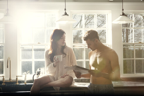 Man reading newspaper while girlfriend sitting with coffee cup on kitchen counter - CAVF10124