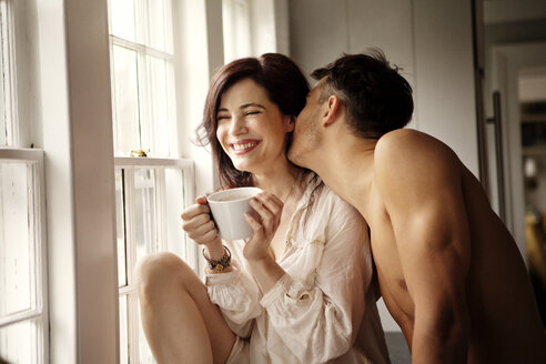 Cheerful couple enjoying while sitting by window at home - CAVF10127