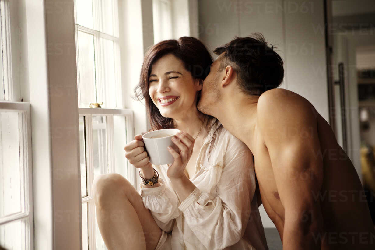Cheerful couple enjoying while sitting by window at home - CAVF10127 - Cavan Images/Westend61