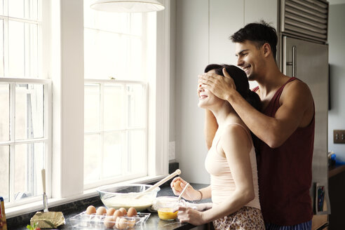 Woman working while man covering eyes at kitchen in home - CAVF10136