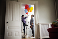 Woman holding helium balloons while standing on staircase by man at home - CAVF10145