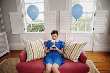 Woman holding cupcake with burning candles while sitting on sofa at home - CAVF10154