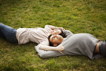 High angle view of man and woman lying on grassy field at park - CAVF10160