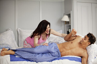 Playful woman pushing man from bed at home - CAVF10169