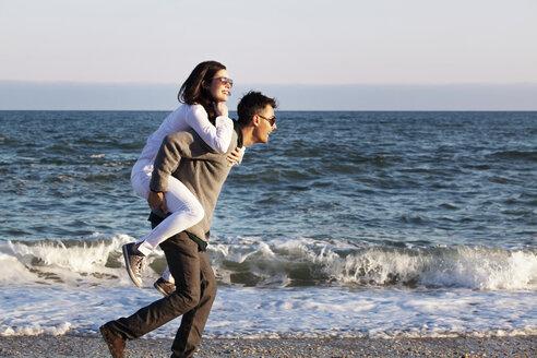 Man piggybacking woman at beach during sunset - CAVF10181