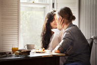 Affectionate couple by breakfast table at home - CAVF10190