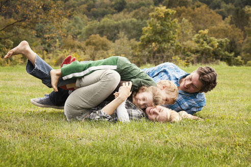 Playful family embracing on grassy field - CAVF10337