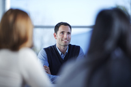 Businessman smiling in meeting - CAIF19455