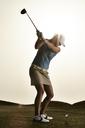 Woman swinging golf club - CAIF19530