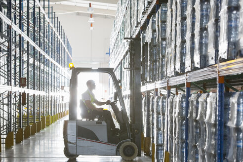 Worker operating forklift in warehouse - CAIF19613