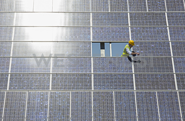 Worker examining solar panel in rural landscape - CAIF19652