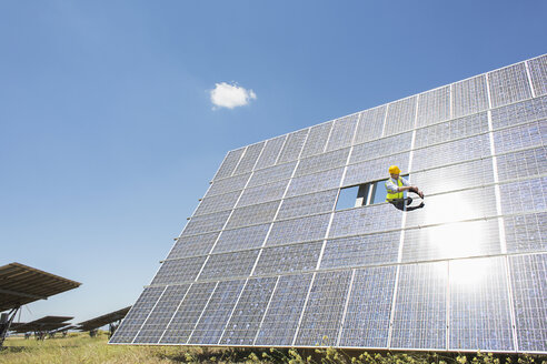 Worker examining solar panel in rural landscape - CAIF19658