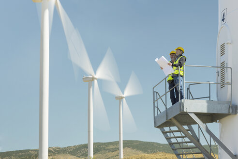 Workers standing on wind turbine in rural landscape - CAIF19661