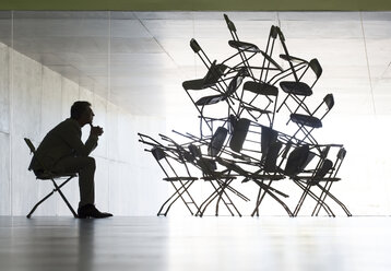 Businessman viewing office chair installation art - CAIF19670