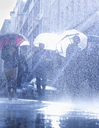 Business people with umbrellas in rain - CAIF19709