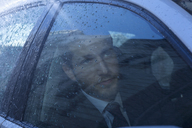 Close up of businessman in car looking up at rain - CAIF19730