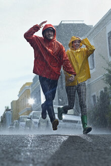 Happy couple in raincoats running down street in rain - CAIF19733