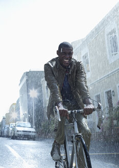 Happy businessman riding bicycle in rain - CAIF19736