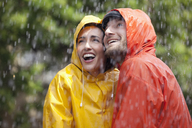 Happy couple in raincoats looking up at rain - CAIF19769