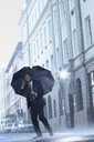 Businessman talking on cell phone under umbrella in rainy street - CAIF19781