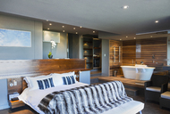 Bed and bathtub in modern master bedroom - CAIF19817