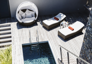 Lounge chairs on wooden deck by modern pool - CAIF19832
