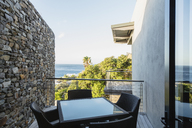 Table and chairs on luxury balcony overlooking ocean - CAIF19877