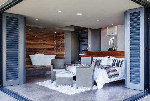 Patio doors open to modern bedroom - CAIF19880