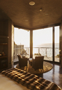 Luxury bedroom overlooking ocean at sunset - CAIF19883