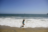 Playful girl running on surfs at Seal Beach against clear sky - CAVF10406