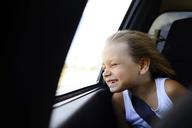 Girl enjoying wind while sitting by window in car - CAVF10427