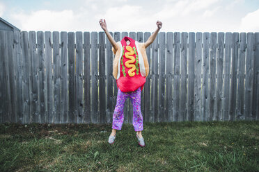 Girl with arms raised jumping while wearing hot dog costume against fence at yard - CAVF10463