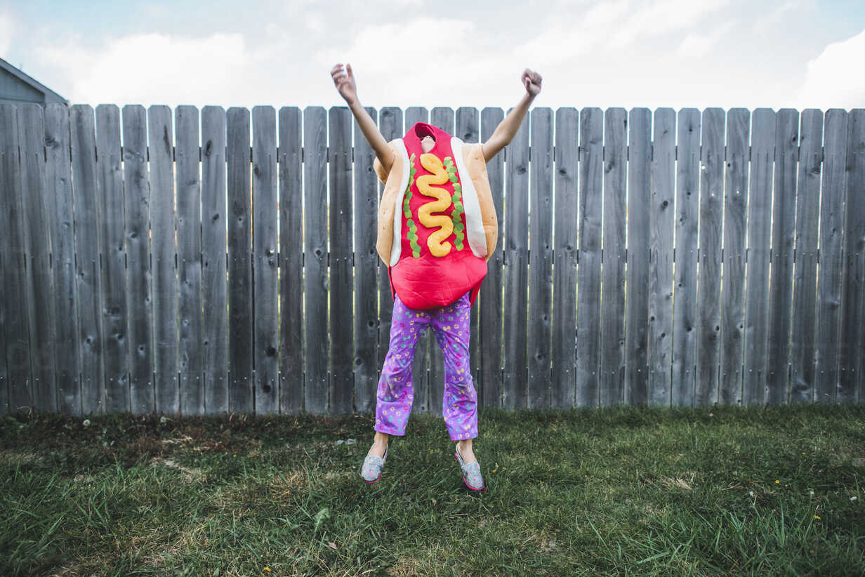 Girl with arms raised jumping while wearing hot dog costume against fence at yard - CAVF10463 - Cavan Images/Westend61