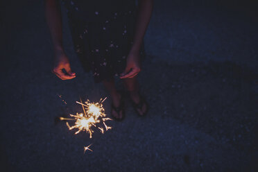 High angle view of girl holding sparklers while standing on field - CAVF10469