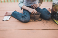 Low section of girl planting seed in pot while sitting on porch - CAVF10484