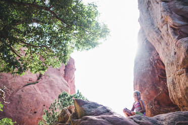 Low angle portrait of girl sitting on rocks against clear sky - CAVF10487