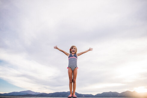 Low angle view of girl with arms outstretched wearing swimwear while standing against cloudy sky - CAVF10493
