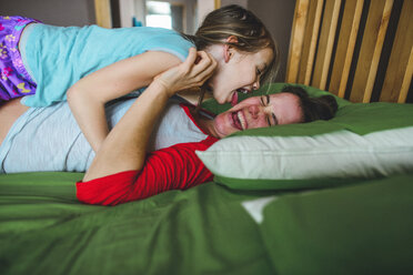 Side view of playful daughter licking mother's cheek on bed at home - CAVF10499