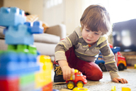 Low angle view of boy playing with toy truck at home - CAVF10526