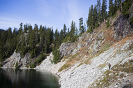 Distant view of hiker and dog walking on mountain by Snow Lake - CAVF10589