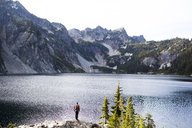 Rear view of hiker standing on rocks against Snow Lake - CAVF10595