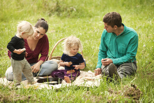Family having food while sitting on grassy field - CAVF10602