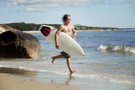 Man carrying surfboard while running on shore - CAVF10608